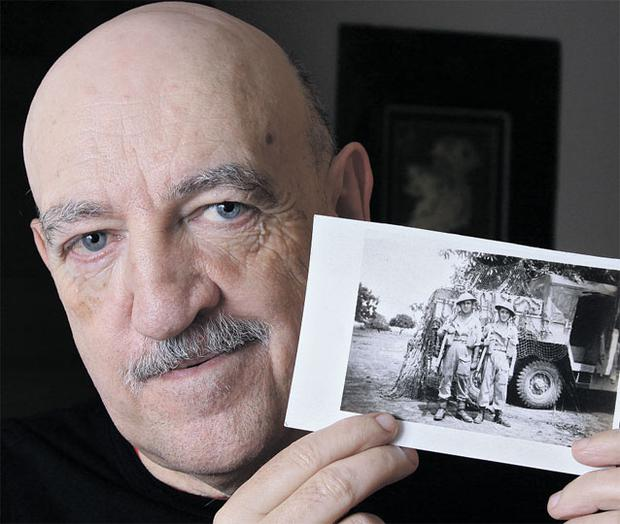 Proud and determined: Paddy Reid wants to see justice for his father and 5,000 others like him, who helped to save Europe from Nazi domination. He holds a picture of his father Paddy and brother Freddie, who both joined the British army