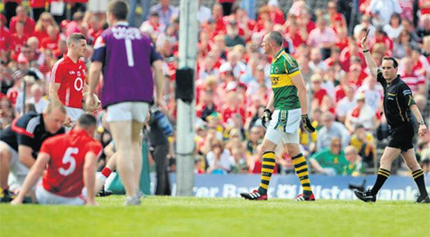 Kerry's Kieran Donaghy is shown a yellow card by referee David Coldrick as Noel O'Leary (5) of Cork, receives attention during the Munster SFC final at Fitzgerald Stadium on Sunday