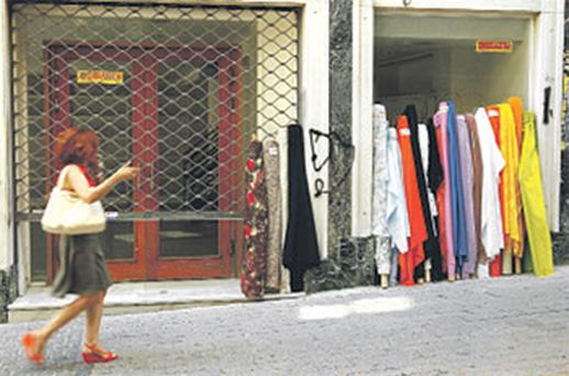 A woman walks past a shop with a 'for rent' sign in Athens, Greece, yesterday