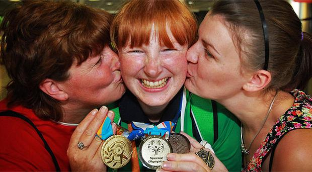 Team Ireland bowler Joyce Haughian from Warrenpoint Co Down, with her three medals, is greeted by her mother Catherine, left, and sister Fiona in the arrivals hall of Dublin Airport. Photo: PA