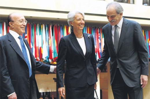 Christine Lagarde is greeted by Shakour Shaalan (left), dean of the executive board of the IMF, and deputy managing director John Lipsky in Washington yesterday