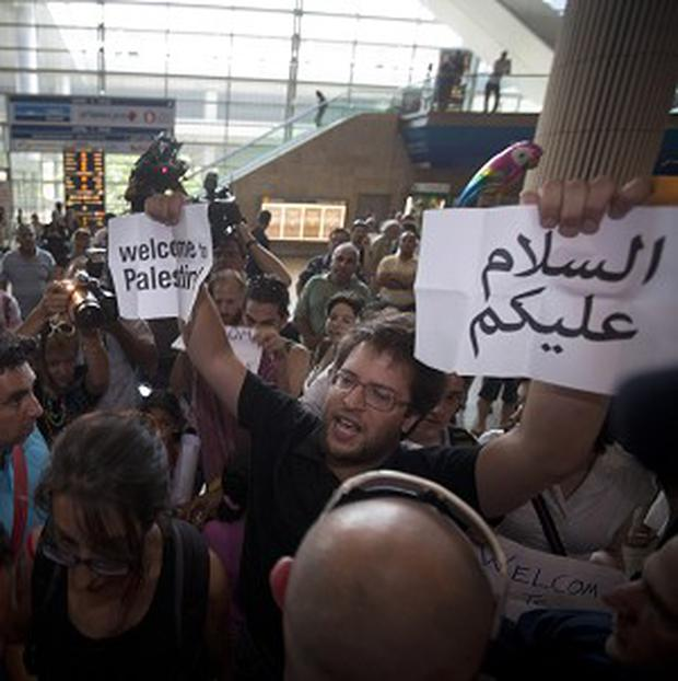 Pro-Palestinian activists hold signs reading Welcome to Palestine at Ben-Gurion International Airport (AP)