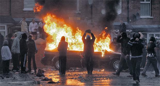 Youths stand near a burning car in the Ardoyne area of north Belfast last night