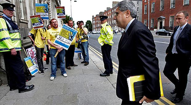 The IMF's Ajai Chopra passes a student protest by 'The Enough Campaign' opposing the EU/IMF quarterly review visit to the Department of Finance yesterday. Photo: Steve Humphreys
