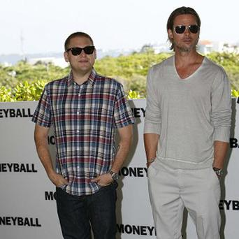 Brad Pitt, pictured with co-star Jonah Hill, likes playing baseball with his kids