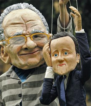 A man dressed as Rupert Murdoch holds a puppet of British Prime Minister David Cameron in London yesterday