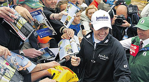 Rory McIlroy signs autographs for fans as he leaves the 18th green after the final practice round for the British Open yesterday