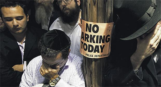 Men weep outside the synagogue in Brooklyn at the funeral of Leiby Kletzky