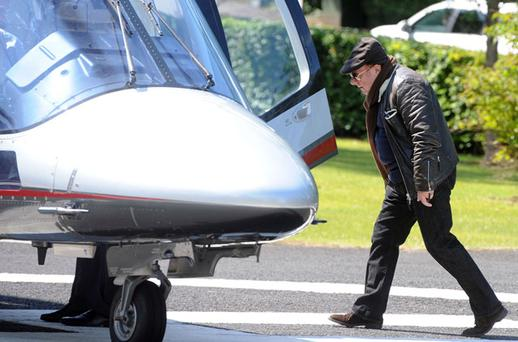 HIGH-FLYER: Singer Van Morrison tries to go unnoticed as he prepares to board a helicopter at the Culloden Hotel outside Holywood, Co Down, last month. Photo: Justin Kernoghan