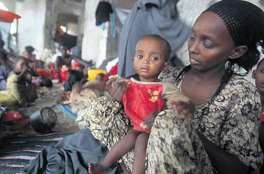 DESPAIR: An internally displaced Somali woman holds her child inside their makeshift shelter in East Africa.