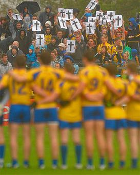 Fans hold crosses to mark their anger as the players line up before the Connacht GAA Football Senior Championship Final