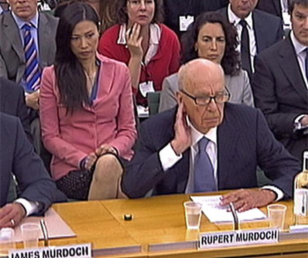 Wendi Deng, wearing a pink cardigan, keeps a close eye on her husband, Rupert Murdoch, at the Commons' Culture, Media and Sport Select Committee