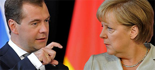 Russian President Dmitry Medvedev and German Chancellor Angela Merkel talk at a signing ceremony after a round of German-Russian consultations in Hanover yesterday