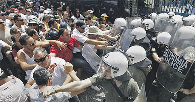 Taxi drivers clash with riot policemen outside the Infrastructure and Transport Ministry in Athens, Greece, yesterday