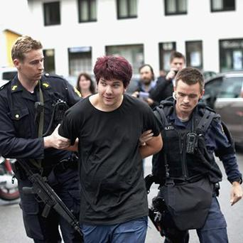 Police detain a young man accused of carrying a knife outside a hotel where Norway's prime minister was meeting families (AP)