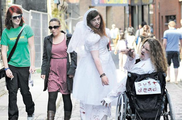 Wheelchair-bound zombie Philip O'Reilly and undead bride Kerrie Costello, both from Wexford, amuse passers by in Temple Bar yesterday