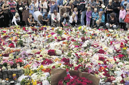 People lay floral tributes after the memorial service yesterday for victims of the Norwegian attacks.