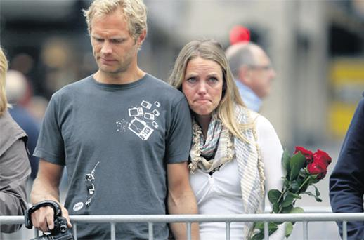 A couple hold hands as they join people paying respects in front of Oslo Cathedral yesterday