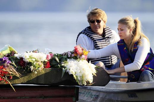 WITH SYMPATHY: Two women take a boat ride on Tyrifjorden lake to leave some flowers near Utoya island, Norway, where Anders Behring Breivik killed more than 70 people over a week ago