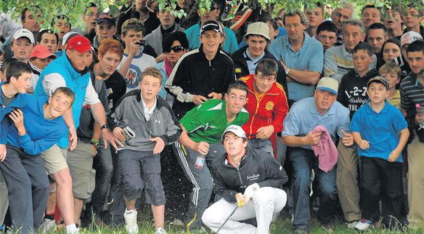 Rory McIlroy and an army of fans anxiously watch his shot from the rough on the ninth hole in Killarney yesterday. Photo: Diarmuid Greene