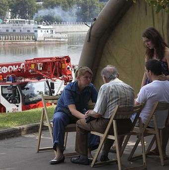 Relatives and friends of victims of a pleasure boat sinking are comforted by an emergency worker in Moscow, Russia (AP)