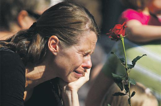 A Norwegian woman pay respects for the victims of attacks outside the Oslo cathedral yesterday