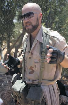 Irish-Libyan rebel fighter Husam Najjair speaks to reporters at a frontline checkpoint near Tiji in western Libya yesterday. Najjair left behind a life as a building contractor in Dublin to become a member of one of the many armed rebel groups