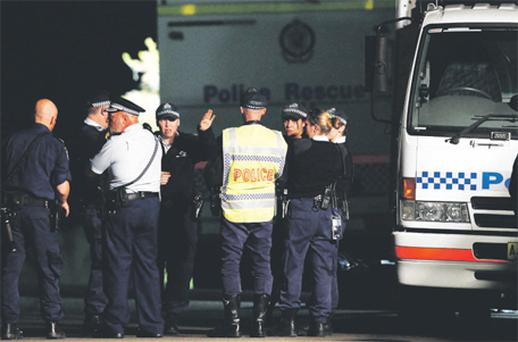 Police and emergency workers at the house where Madeleine Pulver had a bomb attached to her neck