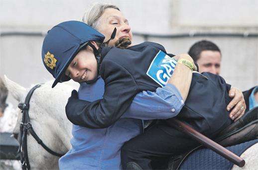 Grace Tyrrell gets a hug from her mother Maria after she helped the garda mini-display team from the Laois hunt pony club to victory at the RDS yesterday