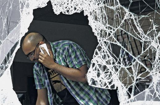 A man looks over the damage caused to a mobile phone shop after the riots