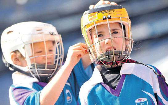 Good example: it is compulsory to wear helmets in hurling, as young players Conor O'Driscoll and Kate McCarthy demonstrate. Now there is a campaign to also try and make mouthguards compulsory for children who play contact sports