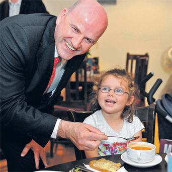 Sean Gallagher tries some of four-year-old Ava Kiernan's soup at The Bakery in Mullingar, Co Westmeath, while canvassing views on the future of the presidency