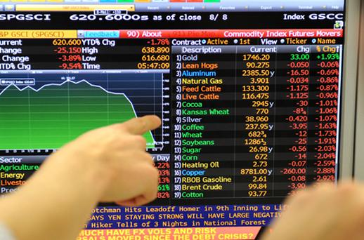 Institutional traders from IG Markets study a screen showing losses in commodities apart from gold which shows a rise of nearly two per cent, on their trading floor in Melbourne. Photo: Getty Images