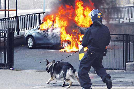 A policeman and his dog walk towards a burning car in central Birmingham yesterday