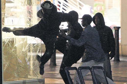 Looters try to kick in the window of a jewellery shop in Birmingham on Monday night