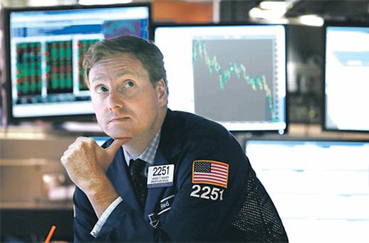 Wall Street woe: A trader works on the floor of the New York Stock Exchange