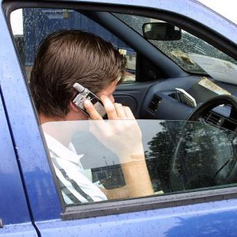A man spotted behind the wheel on a 70mph road as he used two mobile phones has been banned from driving