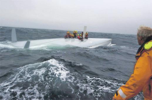Crew on the vessel's upturned hull on Monday