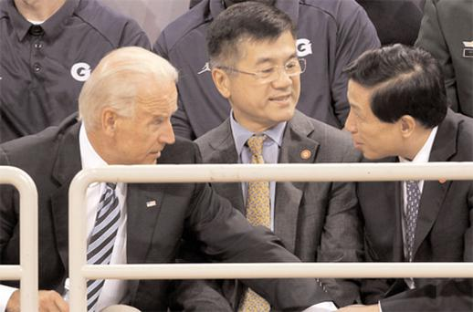 US Vice-President Joe Biden talks to Chinese ambassador to the US, Zhang Yesui (right), as US ambassador to China Gary Locke looks on before a US-China friendly basketball match held at the Olympics sports centre in Beijing yesterday