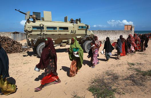 Somalis displaced from their home villages by famine and drought pass an African Union armored vehicle at a feeding center on August 16. Photo: Getty Images