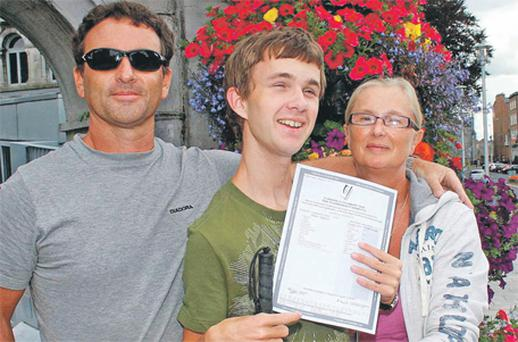 Josh Stundon, with his parents Donal and Mary, holds his Leaving Certificate results outside the People's Park in Limerick city yesterday