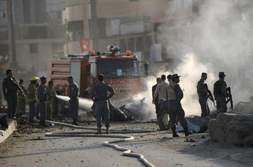 Afghan security personnel and firefighters walk at the site of a suicide attack and a clash at The British Council in Kabul. Photo: Getty Images