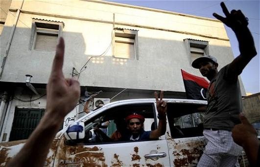 Libyan rebels flash victory signs as they patrol a street in the capital Tripoli. Photo: Getty Images