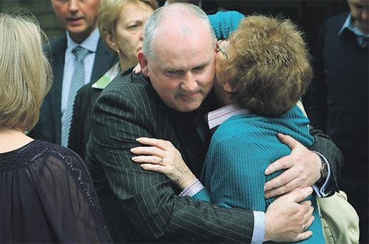 Annabeg Nursing Home owner Brendan O'Connell hugs Patricia Kinsella, wife of the late Patrick Kinsella, outside Dublin Coroner's Court yesterday
