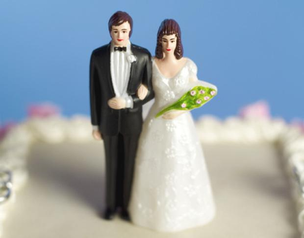Close-up of bride and groom figurine on top of wedding cake