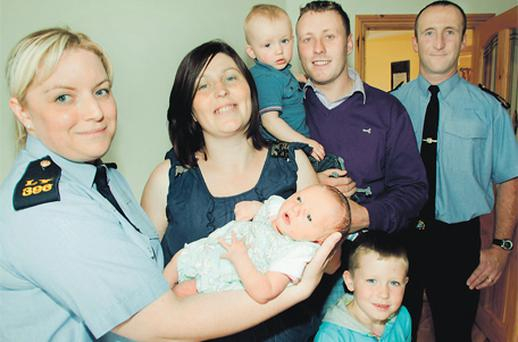 Baby Mia Longworth is the centre of attention after her sudden arrival. From left to right: Garda Nicola Gleeson, mum Niamh, brother Finn, dad Damien, brother Aaron in front, and Garda Kieran Trainor
