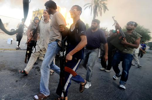 Rebels detain a fighter loyal to Libyan leader Col Gaddafi in the neighbourhood of Abu Salim, in the south of the capital Tripoli. Photo: Getty Images