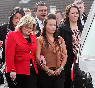 Shannon Graham (centre) daughter of Marian Graham is supported by family members at the funeral of her mother at St Mary's church in Newry, Co Down. Photo: PA