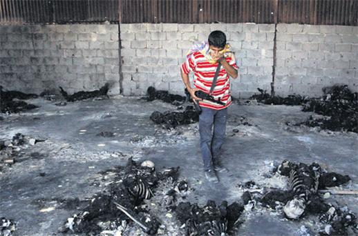 A rebel fighterwalks inside awarehouse containing the remains of at least 53 burned bodies in Tripoli, LIbya, yesterday