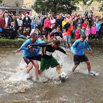 Players take part in the Football in the River match in Bourton-on-the-Water, Gloucestershire